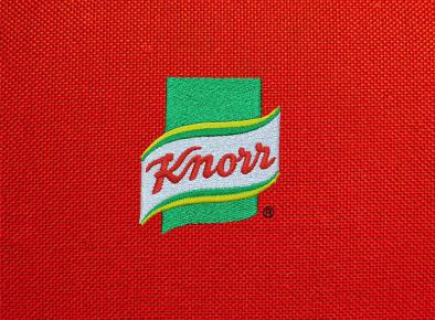 Logo firmy Knorr na czerwonym tle wykonane przy użyciu haftu komputerowego